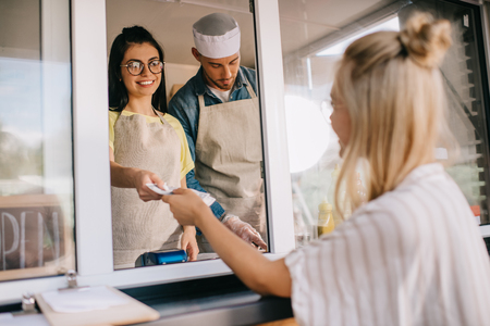 Photo pour young woman paying to smiling worker in food truck - image libre de droit