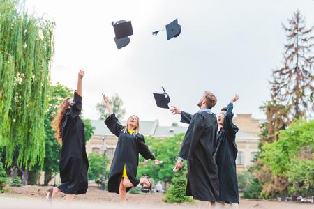 Foto de Happy multicultural graduates with diplomas throwing caps up in park - Imagen libre de derechos