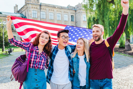Foto de Portrait of smiling multicultural students with american flag in park - Imagen libre de derechos