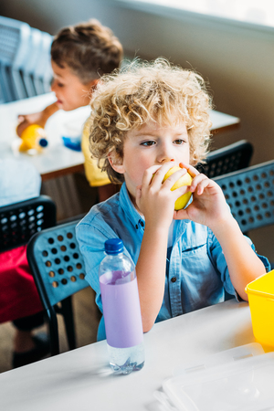 Photo for Adorable curly schoolboy taking lunch together at  school cafeteria - Royalty Free Image