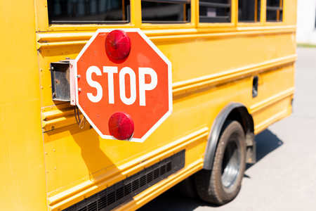 Foto de cropped shot of traditional school bus with stop road sign - Imagen libre de derechos