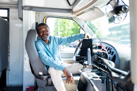 Photo pour smiling mature african american bus driver looking at camera while sitting inside bus - image libre de droit