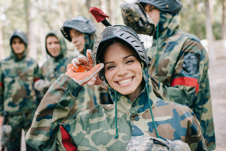 Photo for portrait of laughing female paintballer in uniform looking at camera while her team standing behind outdoors - Royalty Free Image