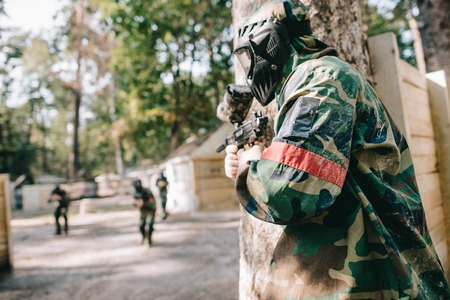 Photo for male paintballer in camouflage and protective mask holding marker gun and hiding behind tree while other team running behind outdoors - Royalty Free Image