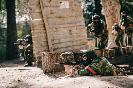 Photo for paintball player laying on ground and aiming by marker gun while his team hiding behind wooden wall outdoors - Royalty Free Image
