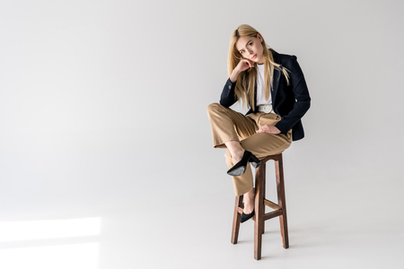 Foto für attractive young blonde woman in stylish clothes sitting on stool and looking at camera on grey - Lizenzfreies Bild