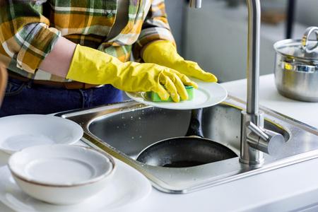 Photo pour cropped image of woman washing plate in kitchen - image libre de droit