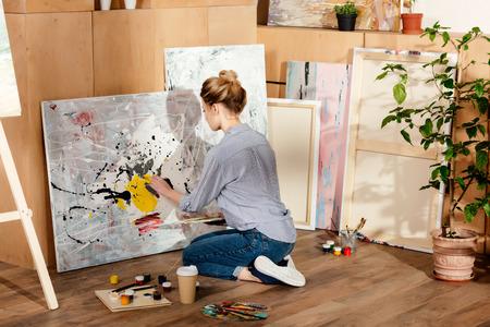 Foto de back view of attractive girl painting in art studio - Imagen libre de derechos