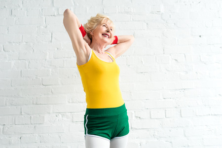 Photo for cheerful sporty senior woman standing with hands behind head - Royalty Free Image