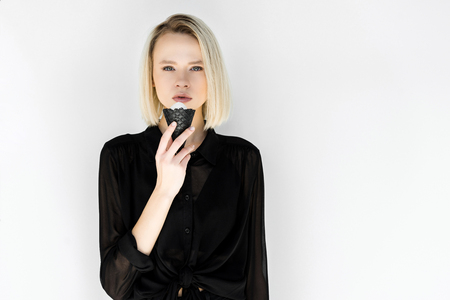 Photo for attractive stylish blonde woman in black clothes eating ice cream in black cone isolated on white - Royalty Free Image