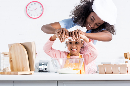 Foto de smiling african american mother and daughter in chef hats putting eggs into bowl together on kitchen - Imagen libre de derechos