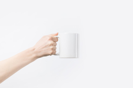 Photo pour cropped shot of woman holding white mug in hand isolated on white - image libre de droit