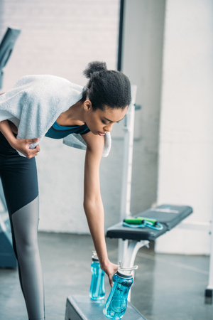 Photo pour african american sportswoman with towel taking sportive water bottle after workout at gym - image libre de droit