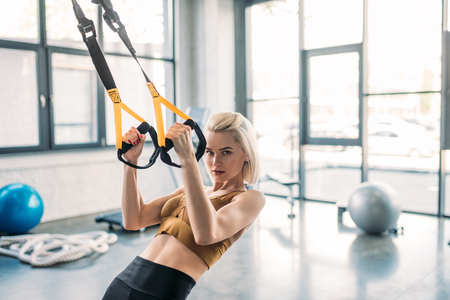 Foto de portrait of young caucasian sportswoman training with resistance bands at gym - Imagen libre de derechos