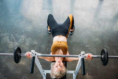Photo pour overhead view of young athletic woman weightlifting barbell at gym - image libre de droit