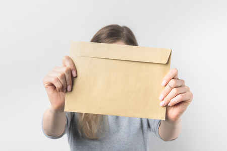 Photo pour obscured view of woman showing blank kraft envelope in hands isolated on white - image libre de droit