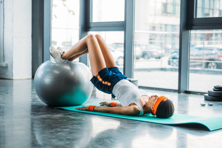 Photo pour side view of african american sportswoman on mat exercising with fitness ball at gym - image libre de droit