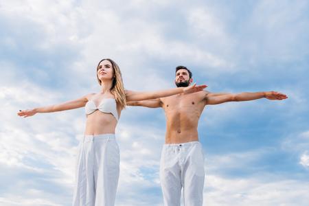 Foto de sporty young couple with outstretched arms meditating under cloudy sky - Imagen libre de derechos