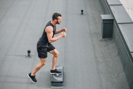 Photo pour side view of handsome sportsman training with step platform on roof - image libre de droit