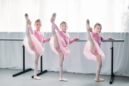 Photo for beautiful little ballet dancers exercising and looking at camera in ballet school - Royalty Free Image