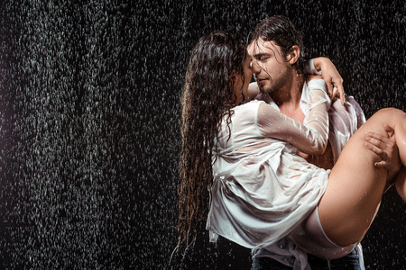 Photo pour portrait of young man holding girlfriend in white shirt while standing under rain isolated on black - image libre de droit