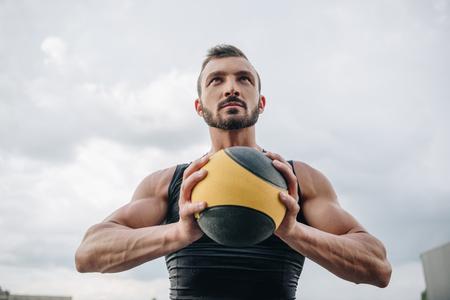 Photo pour handsome sportsman holding medicine ball on roof - image libre de droit