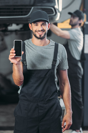 Photo for professional mechanic showing smartphone with blank screen, while colleague working in workshop behind - Royalty Free Image