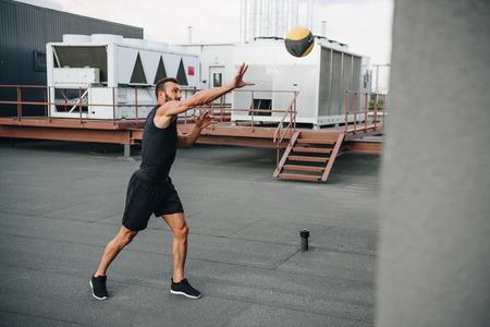 Photo pour handsome sportsman catching medicine ball on roof - image libre de droit
