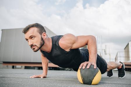 Photo pour handsome sportsman doing push ups with medicine ball on roof - image libre de droit