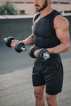Photo pour cropped image of sportsman training with dumbbells on roof - image libre de droit