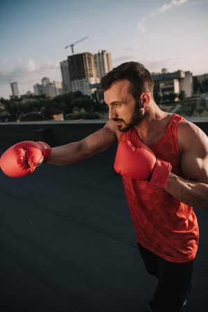 Photo pour side view of handsome boxer training with boxing gloves on roof - image libre de droit