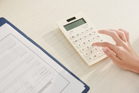 Photo pour cropped view of woman counting finances on calculator at table with insurance claim form - image libre de droit
