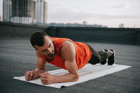 Photo pour handsome sportsman doing plank on yoga mat on roof - image libre de droit