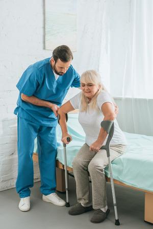 Foto de male nurse helping senior woman with crutches sitting on hospital bed - Imagen libre de derechos