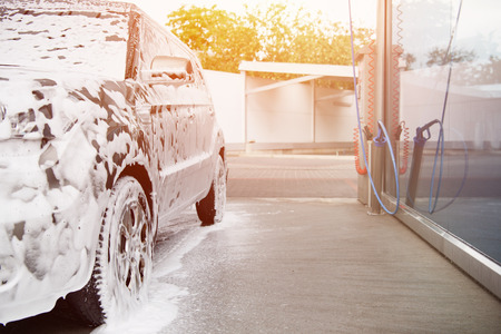Photo pour car in white cleaning foam at car wash during sunset - image libre de droit