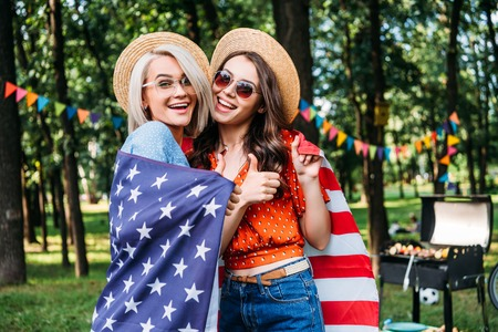 Foto de portrait of happy women in hats and sunglasses with american flag in park - Imagen libre de derechos