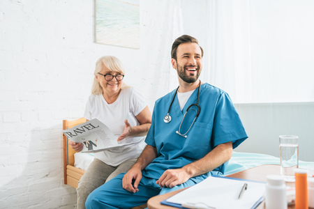 Foto de smiling young doctor with stethoscope sitting on hospital bed with happy senior woman reading travel newspaper - Imagen libre de derechos