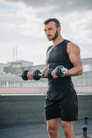 Photo for handsome sportsman training with dumbbells on roof - Royalty Free Image