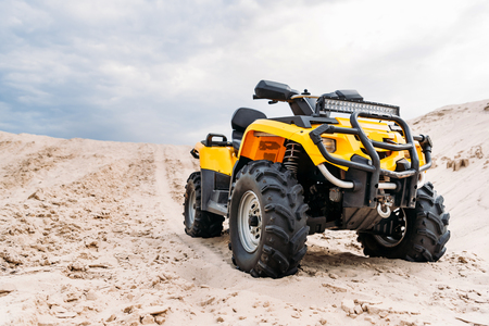 Foto de bottom view of modern yellow all-terrain vehicle standing in desert on cloudy day - Imagen libre de derechos