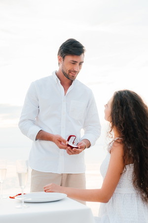 Photo pour handsome man making propose with ring to girlfriend in romantic date - image libre de droit