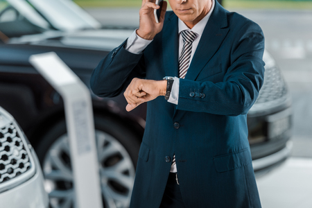 Photo pour cropped shot of adult businessman talking by phone at car dealership salon and looking at wrist watch - image libre de droit