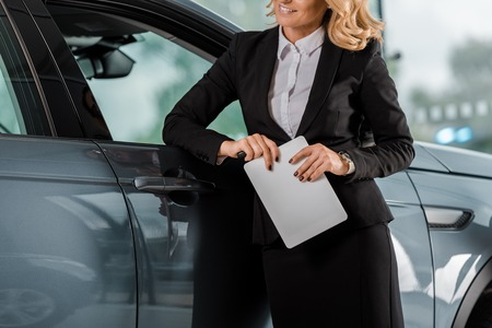 Photo for cropped shot of female car dealer with tablet leaning on car in showroom - Royalty Free Image