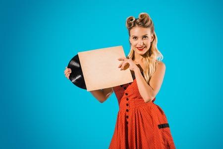 Photo pour portrait of young pin up woman in stylish vintage dress with vinyl record on blue backdrop - image libre de droit