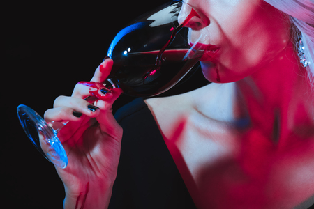 Foto de cropped view of vampire woman drinking blood from wineglass isolated on black - Imagen libre de derechos