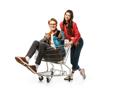 Photo for stylish male hipster in shopping cart showing smartphone with blank screen and doing thumb up while his girlfriend standing behind isolated on white - Royalty Free Image