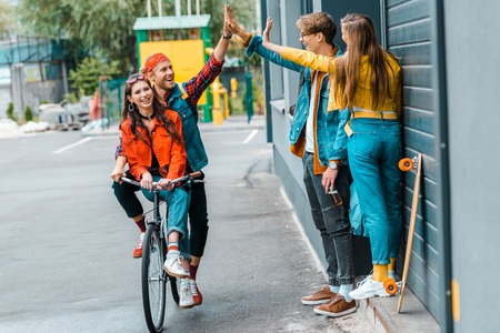Photo pour stylish couple riding bicycle and giving highfive to friends on street - image libre de droit