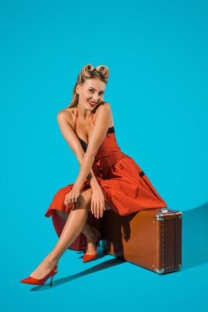 Photo pour smiling pin up woman in retro dress sitting on suitcase on blue backdrop - image libre de droit