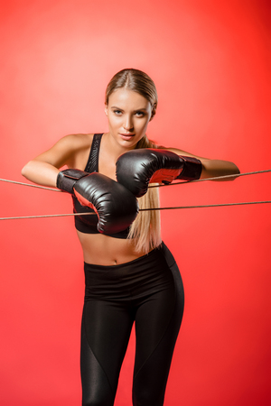 Foto de attractive boxer with boxing gloves leaning on ropes and looking at camera isolated on red - Imagen libre de derechos