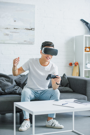 Foto de excited young man in virtual reality headset playing with joystick at home - Imagen libre de derechos