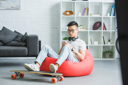 Photo pour handsome young asian man sitting in bean bag chair and using smartphone at home - image libre de droit